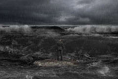 Businessman standing on rock facing oncoming waves with dark oce Stock Photography