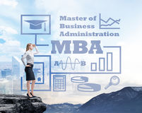 Businessman standing on a rock and looking at the future perspectives of MBA degree. Royalty Free Stock Images