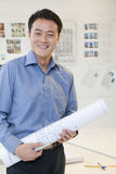 Businessman standing with rolled up blueprint in the office, portrait Stock Image