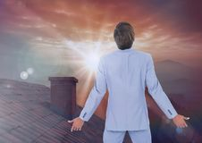 Businessman standing on Roof with chimney and epic twilight sunset Royalty Free Stock Photography