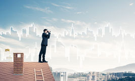 Businessman standing on roof and looking in binoculars. Mixed me Stock Images
