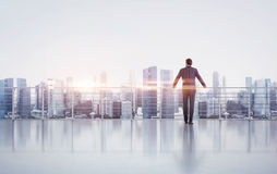 Businessman standing on a roof and looking at. City Royalty Free Stock Image