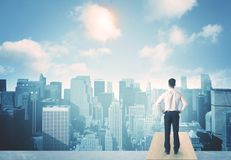 Looking at future city. Businessman standing on a roof and looking at future city Stock Image