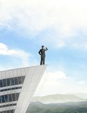 Businessman standing on roof Royalty Free Stock Photo