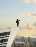 Businessman standing on roof Royalty Free Stock Image