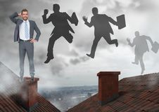 Businessman standing on Roofs and businessmen silhouettes jumping with chimney and cloudy city. Digital composite of Businessman standing on Roofs and Royalty Free Stock Image