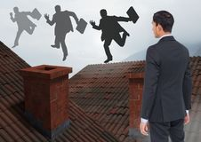 Businessman standing on Roofs with chimney and fog looking at businessman silhouettes running with b. Digital composite of Businessman standing on Roofs with Stock Photo