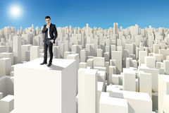 Businessman standing on the rooftop of a 3d skyscraper Royalty Free Stock Images