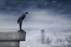 Businessman standing on rooftop and look down stock photos