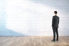 Businessman standing in room. With empty white brick wall and wooden floor. 3D Rendering Royalty Free Stock Image