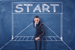 Businessman standing in running position on blue blackboard background with chalk drawing of starting gate. Royalty Free Stock Photos