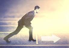 Businessman standing on running track stock images