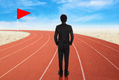 Businessman standing on running track and looking to goal Stock Images