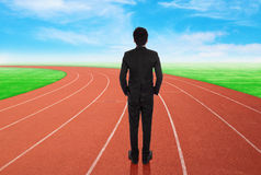 Businessman standing on running track and looking to goal Royalty Free Stock Images