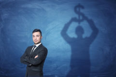 Businessman standing and shadow on the blackboard behind him holding dollar sign above his head Stock Images