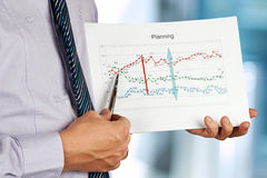 Businessman standing and showing graphic. Stock Image