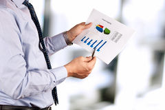 Businessman standing and showing graphics, diagram. Stock Photos