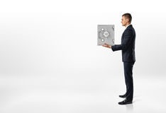 Businessman standing sideways and holding gray metal safety box in his hands on the white background. Royalty Free Stock Photos