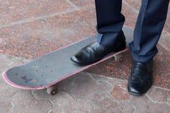 Businessman standing on skateboard Stock Images