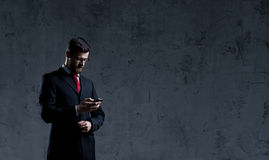Businessman standing with smartphone over dark wall background. Stock Images