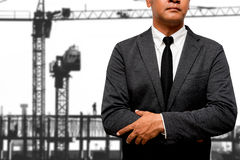 Businessman standing with smoke in background. Businessman standing with construction cranes in background Royalty Free Stock Photos