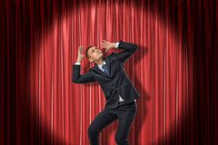 Businessman standing in spotlight near red stage curtain, leaning aside, looking up and protecting head with hands from stock photography