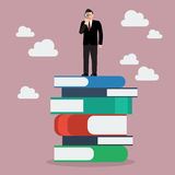 Businessman standing on stack of books with a magnifying glass. Business vision Royalty Free Stock Photos