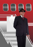 Businessman standing on stairs to airplane. Wearing a hat Stock Images