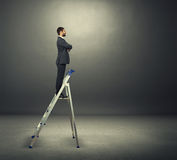 Businessman standing on the stepladder Stock Photo
