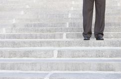 Businessman standing on steps. In the middle of the staircase Stock Photos