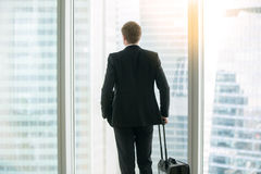 Businessman standing with suitcase near the window. Young businessman with suitcase standing looking at the full length window, before a trip undertaken for work royalty free stock photography