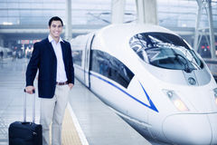 Businessman standing with a suitcase on the railroad platform by a high speed train in Beijing royalty free stock images