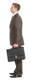 Businessman standing with suitcase Royalty Free Stock Photos