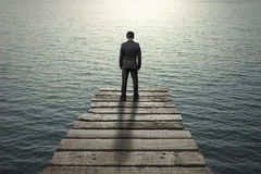 Businessman standing and thinking on old wooden pier to the sea. With sunlight reflection Stock Photo