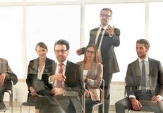 Businessman standing to address colleagues at meeting stock photos