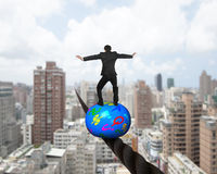 Businessman standing on top of ball balancing on wire Stock Image