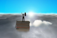 Businessman standing on top of books with cloudy below Royalty Free Stock Photo
