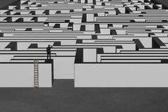 Businessman standing on top of maze wall with wooden ladder Royalty Free Stock Photography