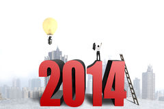 Businessman standing on top of 2014 structure, another in balloo Stock Photos