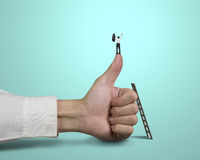 Businessman standing on top of thumb with 2 hands up Stock Photo