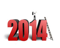 Businessman standing on top of 2014 with wooden stepladder Stock Photo