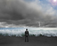 Businessman standing toward waves and cludy sky with Lightning ,. Thunder to challenge dangerous situation Stock Image