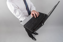 Businessman standing, typing on laptop computer Royalty Free Stock Images