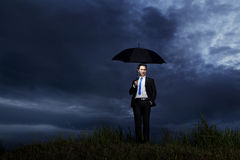 Businessman standing with umbrella Royalty Free Stock Photo