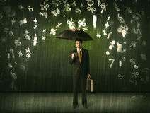 Businessman standing with umbrella and 3d numbers raining concep Royalty Free Stock Photos
