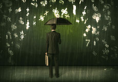 Businessman standing with umbrella and 3d numbers raining concep Stock Image