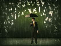 Businessman standing with umbrella and 3d numbers raining concep Stock Photos