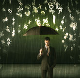 Businessman standing with umbrella and 3d numbers raining concep Stock Images