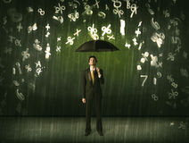 Businessman standing with umbrella and 3d numbers raining concep Royalty Free Stock Photography