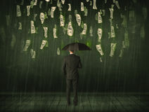 Businessman standing with umbrella in dollar bill rain concept Royalty Free Stock Image